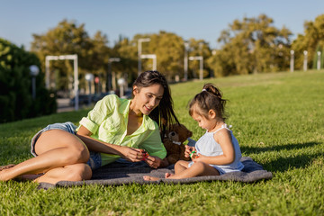 Happy mother playing with daughter on a blanket in park