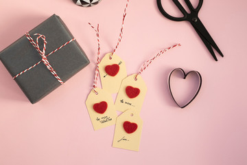 Valentine gift and self-made tags on pink background