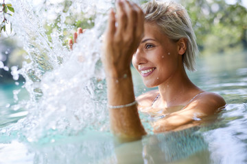 Beautiful woman bathing in a lake, splashing water