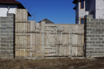 gray old wooden gate and brick fence on rural street
