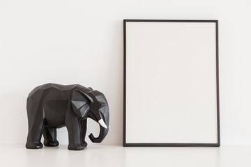 Frame mock up and elephant decoration on bright wall.