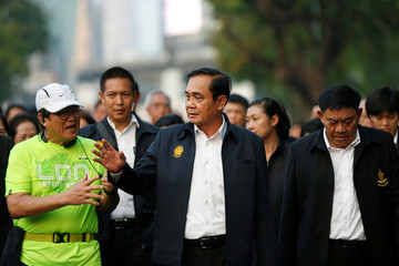 Thailand's Prime Minister Prayut Chan-o-cha talks with a man as he visits Lumphini Park ahead of the general election, in Bangkok