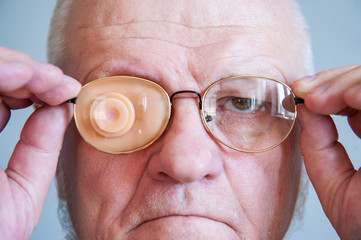 Elderly man in glases with Occluder. Ortopad Man Eye Patces nozzle for glasses for treating strabismus (lazy eye).Senior with beards