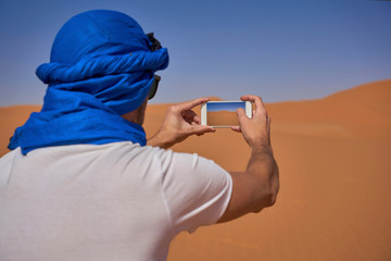 Morocco, back view of man wearing  blue tuban taking photo with smartphone in the desert