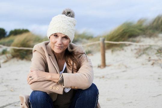 Spain, Menorca, portrait of smiling senior woman wearing bobble hat on the beach in winter