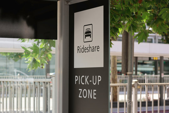 Black and white rideshare pick up zone sign