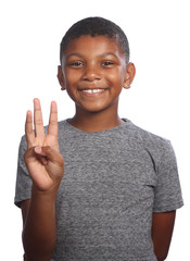 Smiling black boy showing number three on fingers
