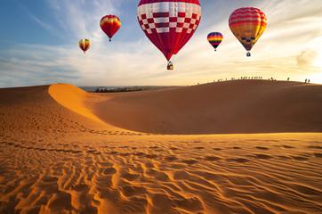 Poster Ballon Hot air balloons in the desert at sunset background