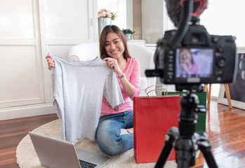 Asian young female blogger recording vlog video with review cloths T-shirt at home online influencer on social media concept.live streaming viral