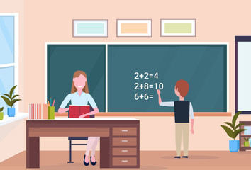 woman teacher sitting at desk schoolboy solving math problem on chalkboard during lesson education concept modern school classroom interior full length horizontal flat