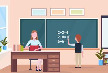 woman teacher sitting at desk schoolboy solving math problem on chalkboard during lesson education concept modern school classroom interior full length horizontal flat
