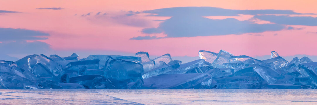 blue toros of Baikal against the background of the pink sky of the dawn and purple clouds. Wide panorama