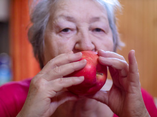 Portrait of mature woman smiling with red apple in hands