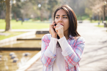 Shocked worried girl talking on phone outdoors