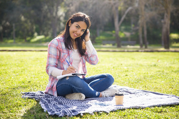 Smiling positive college girl working on essay outdoors