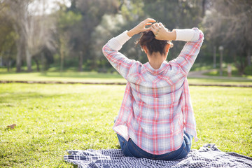Student girl in checked shirt and jeans enjoying leisure in park