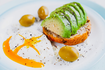 Healthy food concept: toast with avocado, green olives and poached egg
