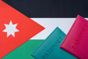 Against the background of the flag of Jordan two passports.