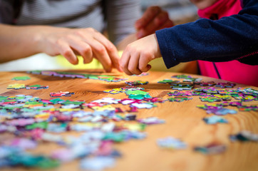 Hands of a little child and parent plying jigsaw puzzle game on a  table