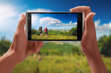 Couple of hikers on a screen of smartphone