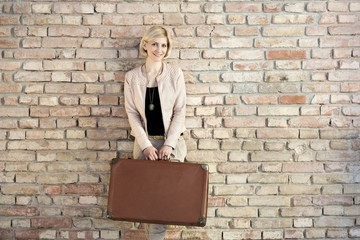 Happy woman holding suitcase