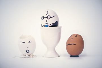 Angry boss and two employees in the form of white and dark eggs.  Creative. Concept