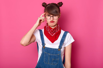 Close up portrait of brunette student, wears round eyewear and red bandana on neck, curves lips, keeps fore finger on temple, poses against pink background. Copy space for your advertisment.