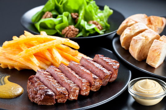Appetising steak slices served with fries , green salad and baguette on a black plate.