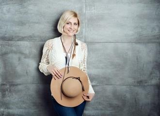 Stylish woman front of grey wall