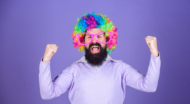 Feel free to express yourself. Having fun. Holiday fun and carnival concept. Man bearded wear colorful wig and funny glasses on violet background. Clown and circus. Party fun. Enjoy being crazy
