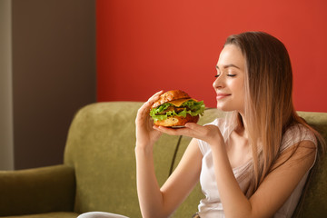 Beautiful young woman with tasty burger sitting on sofa