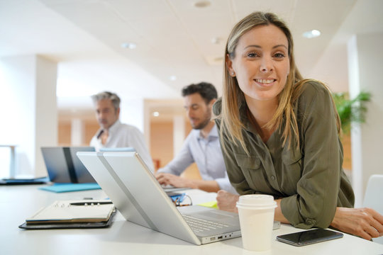 Female startup team member smiling at camera in office
