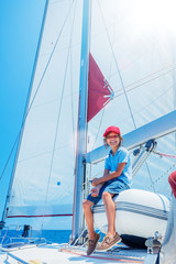 Little boy on board of sailing yacht on summer cruise. Travel adventure, yachting with child on family vacation.