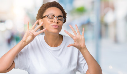 Beautiful young african american woman wearing glasses over isolated background showing and pointing up with fingers number nine while smiling confident and happy.