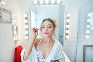 Young woman applying makeup at home