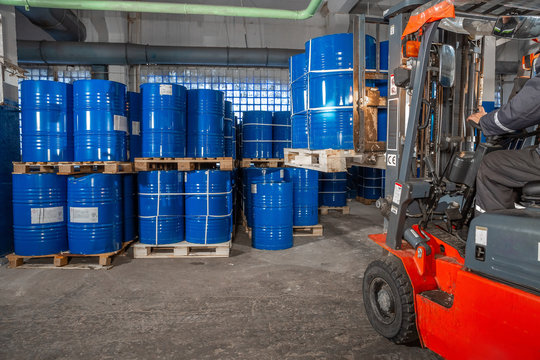 blue barrels and red forklift in warehouse