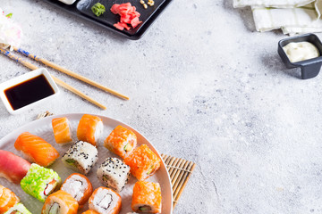 Various Fresh and delicious sushi set on white slate with wooden sticks, sauce on light stone background , flat lay
