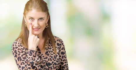 Beautiful middle age mature rich woman wearing leopard dress over isolated background Pointing to the eye watching you gesture, suspicious expression