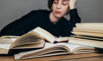 Student schläft über einem Stapel Bücher ein