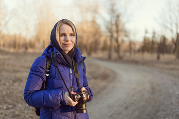 A woman photographer holds a camera in her hands. The concept of a woman photojournalist.