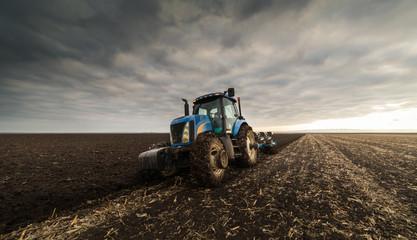 Farmer plowing stubble field