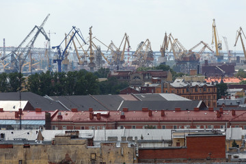 City view from the roof of the building to the river port and cranes at the shipyard for loading cargo on large sea cargo ships at the container terminal in the port of St. Petersburg