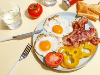 Simple breakfast. Fried egg with bacon, bell pepper and toast on a plate.