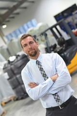 erfolgreicher Geschäftsmann im Warenlager einer Spedition // successful businessman in the warehouse of a forwarding agency