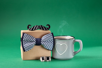 Father's day present gift box with mug coffee on green background.Holiday present concept.