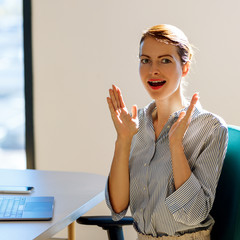 Surprised business woman sitting at the desk in office.