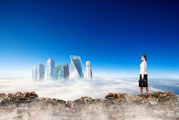 Business woman stands on the edge of mountain and looking on city.