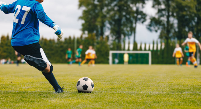 Soccer Football Goalkeeper Goal Kick. Goalie Kick on the Pitch During Match. Goalkeeper Restarting Play in a Game