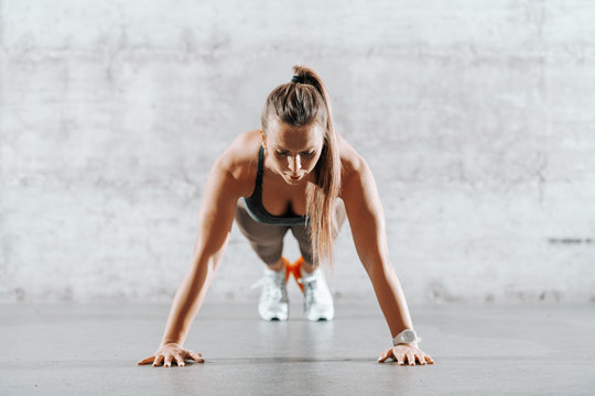Muscular focused brunette with ponytail and in sportswear doing push ups in front of brick wall inn gym.