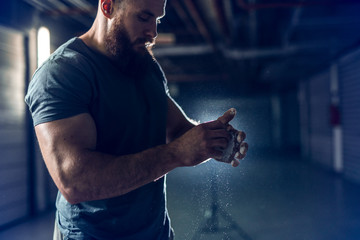 Side view of muscular bearded man clapping hands. Chalk all around.